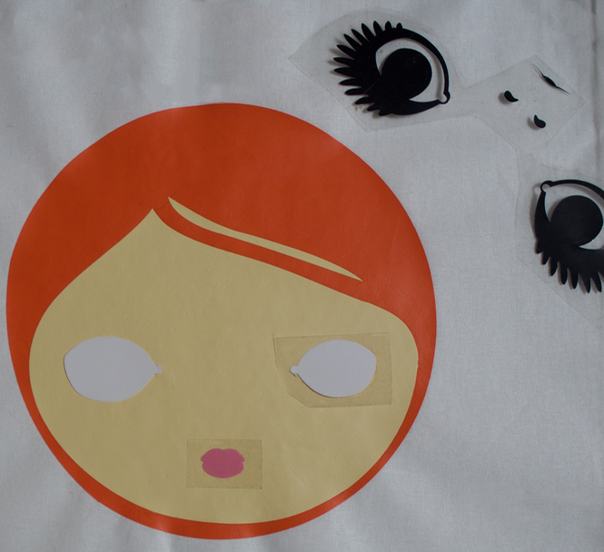 Positioning htv pieces onto Mod girl face tote bag