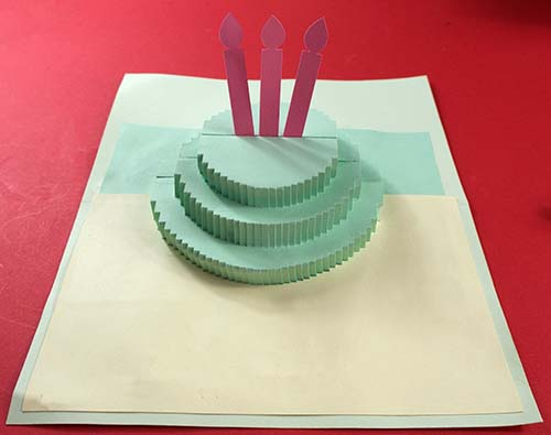 Applying card interior to pop-up cake card