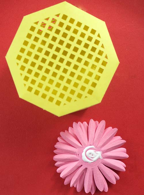 Applying gerbera to lid of octagonal box