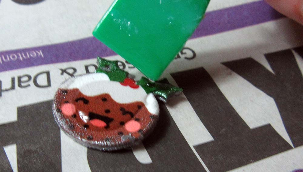 applying epoxy to christmas charm cricut
